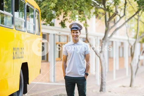 Smiling bus driver standing with hands in pocket in front of bus