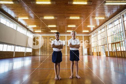 Boys standing with arms crossed in basketball court