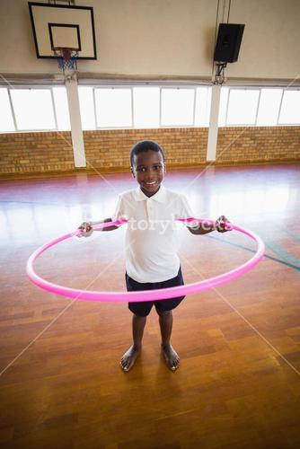 Portrait of boy playing with hula hoop in school gym