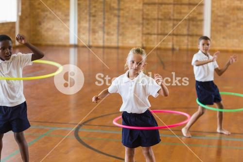 Students playing with hula hoop in school gym