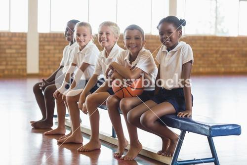 Smiling students sitting on bench with basketball