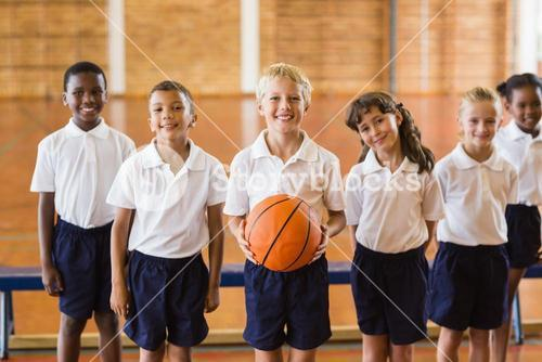 Smiling students standing with basketball