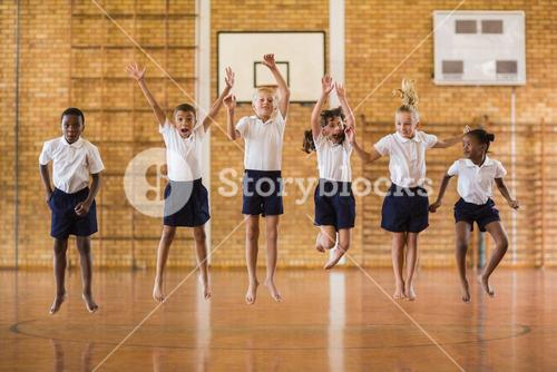 Group of students jumping in school gym
