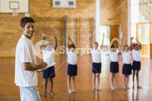 Sports teacher writing notes on clipboard while students exercising