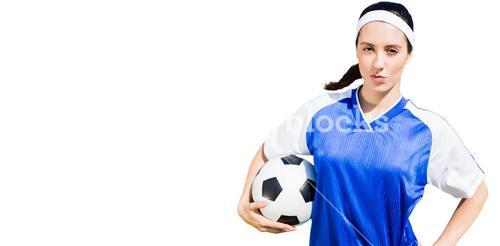 Woman football player posing with football on a white backgorund