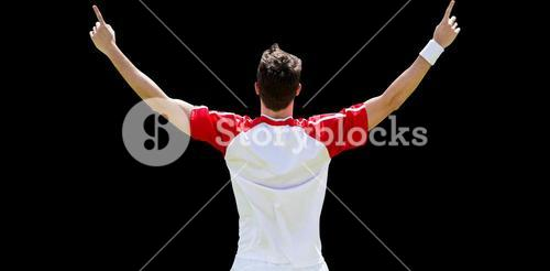 Rear view of sportsman raising arms for the victory