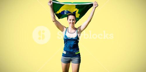 Composite image of front view of sportswoman raising brazilian flag
