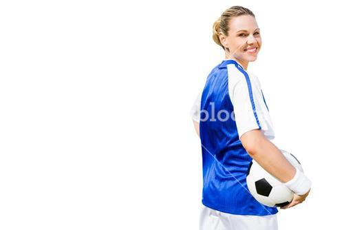 Woman soccer player posing with a ball