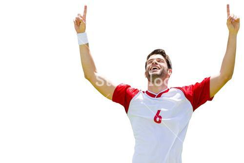 Portrait of happy sportsman is raising arms of the victory