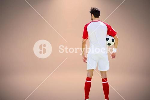 Composite image of rear view of man wearing soccer uniform and holding soccer ball