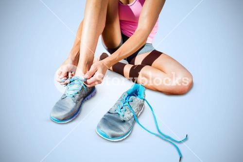 Composite image of athletic woman lacing up shoes