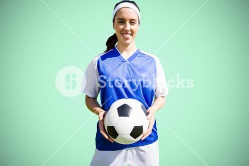 Composite image of woman holding soccer ball