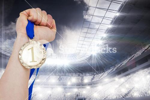 Composite image of close-up of hand holding olympic gold medal