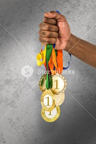 Composite image of athlete holding gold medals after victory