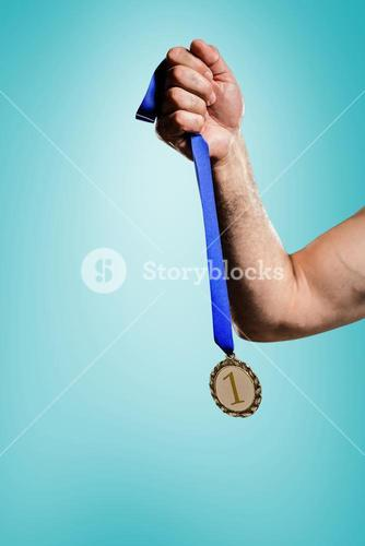 Composite image of hand holding olympic gold medal