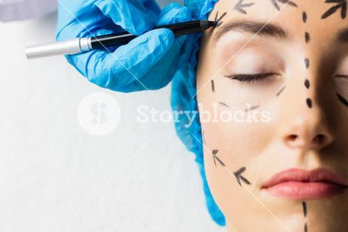 Peaceful young patient with dotted lines on the face
