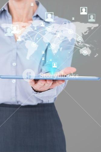 Composite image of businesswoman is holding a tablet with a hologram