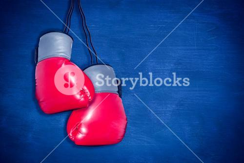 Composite image of boxing gloves attached to white background