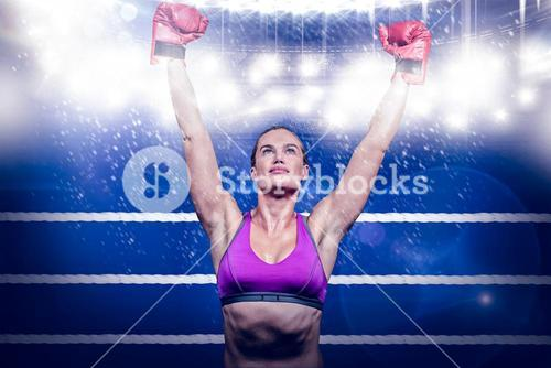 Composite image of winner female boxer with arms raised