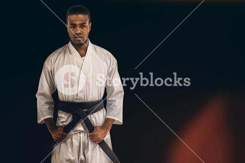 Composite image of fighter tightening karate belt