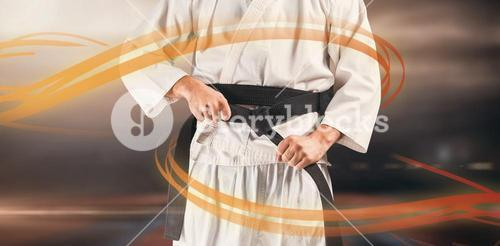 Composite image of mid section of fighter tightening karate belt