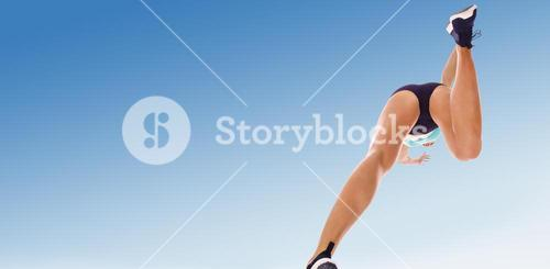 Composite image of low angle female athlete jumping