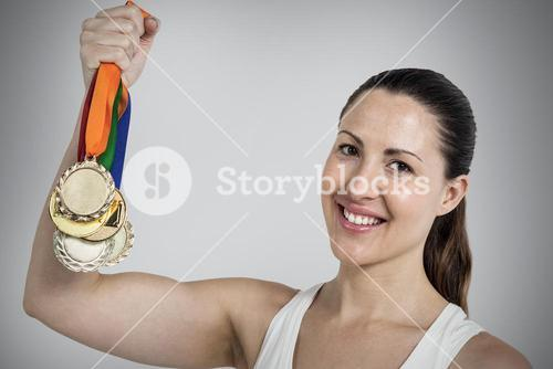 Composite image of female athlete posing with gold medals after victory