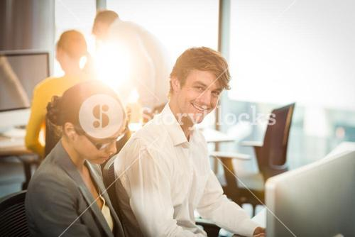 Businessman working on computer with coworker