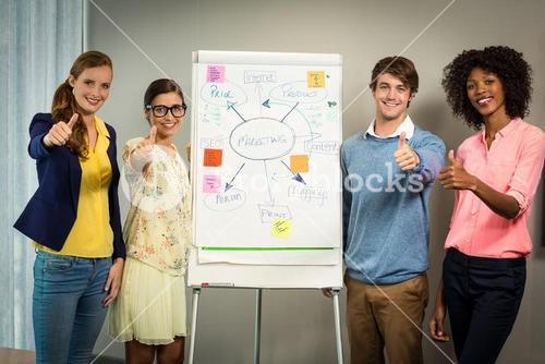 Business executives standing with flowchart on white board