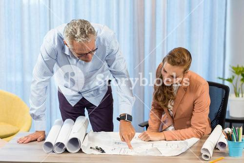 Businesswoman and coworker discussing blueprint