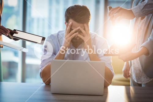 Frustrated businessman sitting on desk with hand on head
