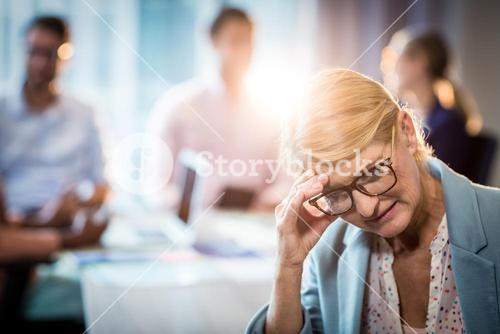 Frustrated businesswoman sitting with hand on head