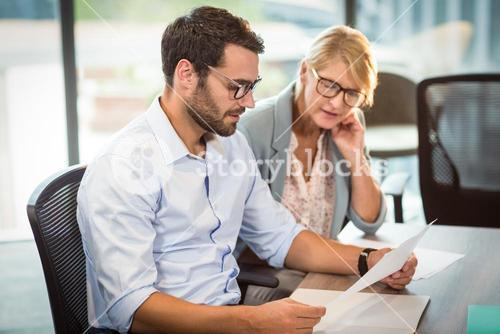 Businesswoman and a colleague reading document