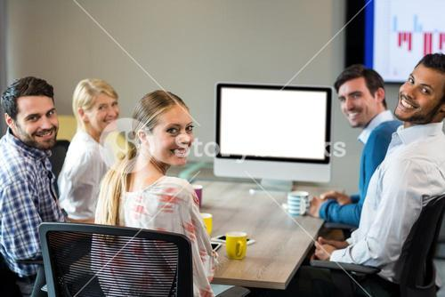 Business people smiling at camera during a video conference