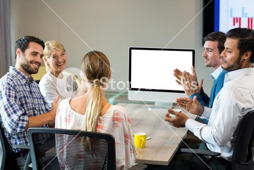 Coworkers applauding a colleague during a video conference