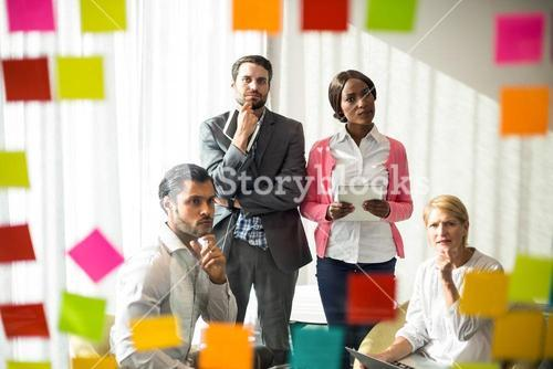 Business people looking at adhesive notes