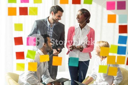 Business people discussing over adhesive notes