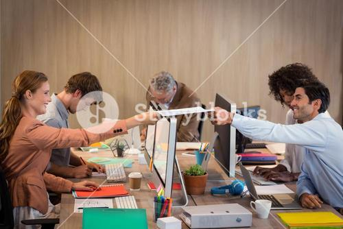 Businessman passing a file to his colleague