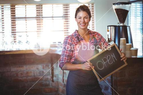 Waitress holding a sign with open
