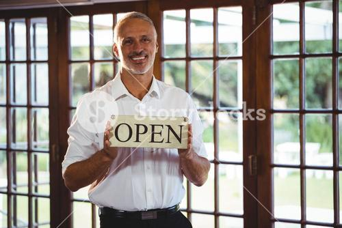 Smiling man holding a sign with open
