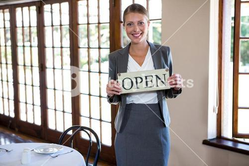 Woman holding a sign with open