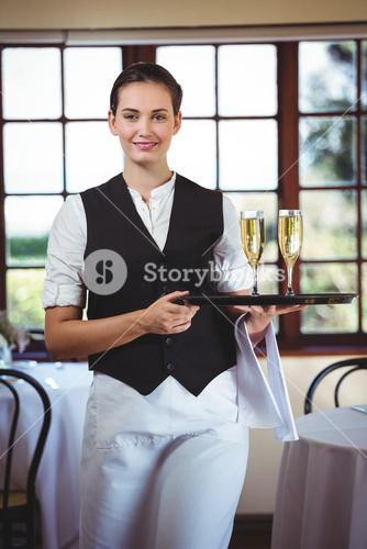 Portrait of waitress holding serving tray with champagne flutes