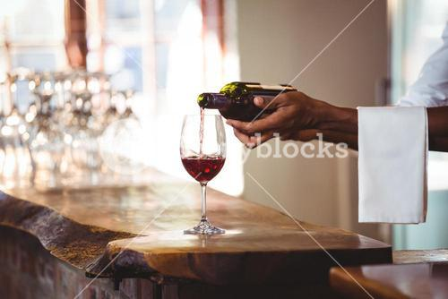 Bartender pouring red wine in a glass