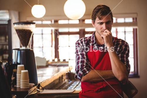 Thoughtful waiter standing at counter