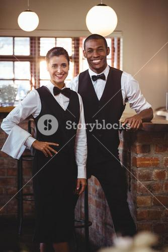 Portrait of waiter and waitress standing together