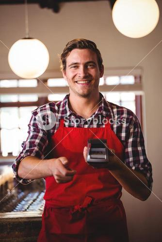 Portrait of waiter showing credit card machine