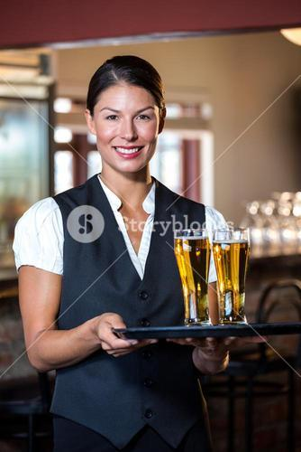 Portrait of waitress holding serving tray with two glass of beer