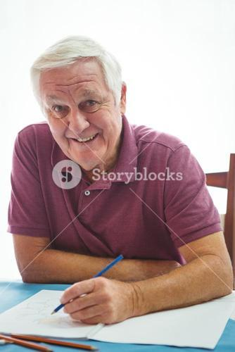 Portrait of  a smiling retired man writing on white paper