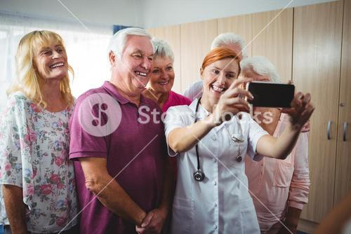 Retired people taking a selfie with a nurse