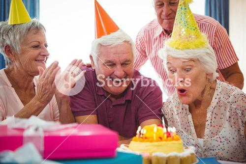 Senior woman blow on birthday cake